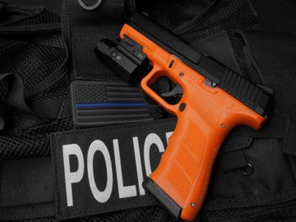Left Side of Blaze Orange ATP-LE2 KWA Gas Airsoft Pistol Against Police Uniform